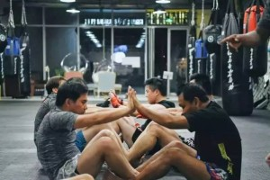 在拳馆,学员两两协作完成仰卧起坐